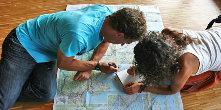 Two people drawing an Andalusia Travel Itinerary on a map