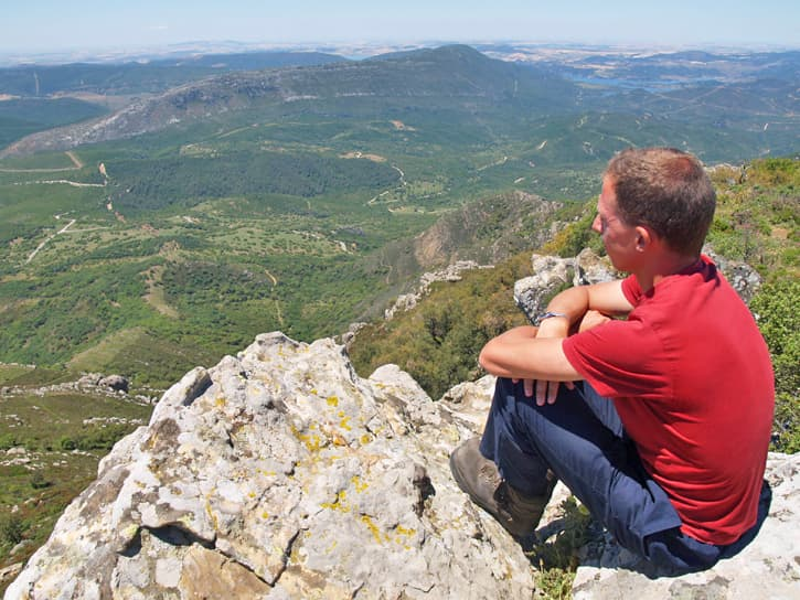 A man on top a mountain looking at the horizon